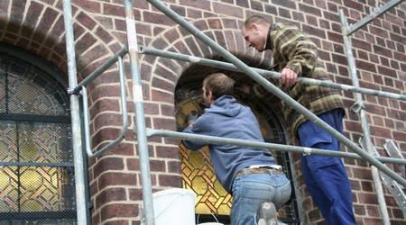 Andy Michael und Mario Müller setzen das letzte wieder aufbereitete Bleiglasfenster ein.