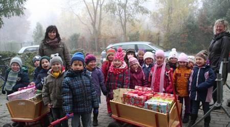 """Erzieherin Kerstin Sagasser (l.), Kita-Leiterin Ines Lüttig (r.) und die Mädchen und Jungen der Marienkäfer-Gruppe der Kita """"Spielkiste"""" brachten zwei """"Wagenladungen"""" voll Geschenke."""