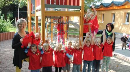 """Passen perfekt: Die Mädchen und Jungen der Kita """"Spielkiste"""" freuen sich gemeinsam mit Leiterin Ines Lüttig (l.)  und Elke Mißbach von KTSB Bau (r.) über die neuen T-Shirts."""