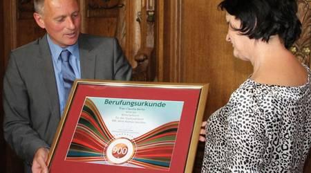 Aus den Händen von Köthens Oberbürgermeister Kurt-Jürgen Zander erhält Claudia Berlin die Berufungsurkunde zur Botschafterin des Stadtjubiläums.